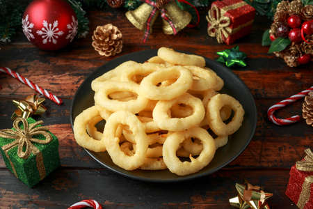 Christmas Onion rings with decoration, gifts, green tree branch on wooden rustic table