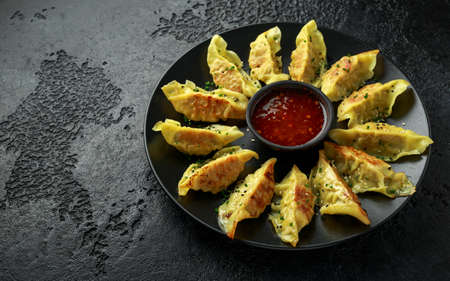 Fried yaki Gyoza served on stone plate with sweet chilli sauce and sesame seeds Stock Photo