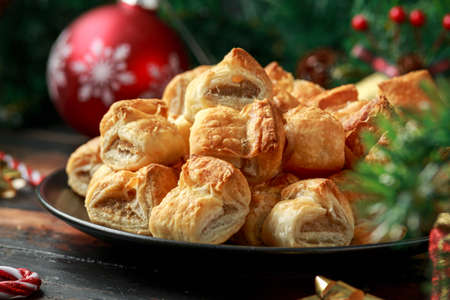 Christmas Sausage Rolls with decoration, gifts, green tree branch on wooden rustic table