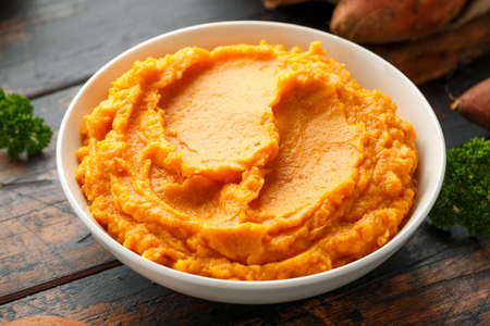 Mashed Sweet Potatoes in white bowl on wooden rustic table. Healthy food