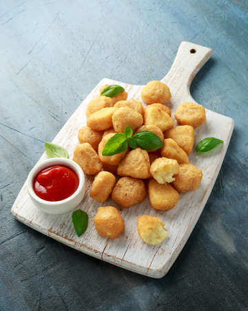Fried mozzarella, cheddar cheese bites, balls with ketchup on white wooden board Stock fotó