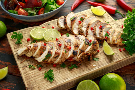 Homemade Grilled Chicken Breast in lime sauce with herbs on wooden board