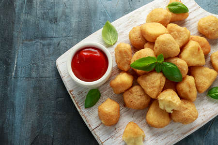 Fried mozzarella, cheddar cheese bites, balls with ketchup on white wooden board Stockfoto