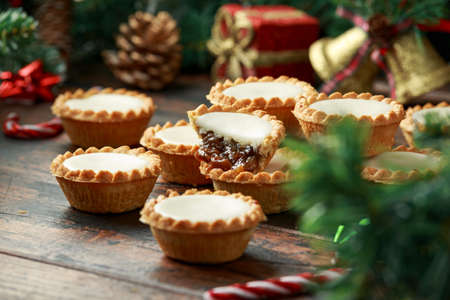 British Christmas iced mince pies with decoration, gifts, green tree branch on wooden rustic table Stockfoto