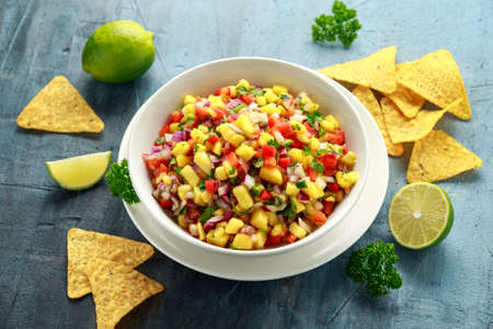 Bowl of fresh Mango Salsa with nachos chips and herbs. Healthy Vegan, Vegetables food.