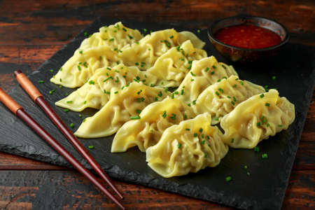 Steamed yaki Gyoza served on stone board with sweet chilli sauce and sesame seeds