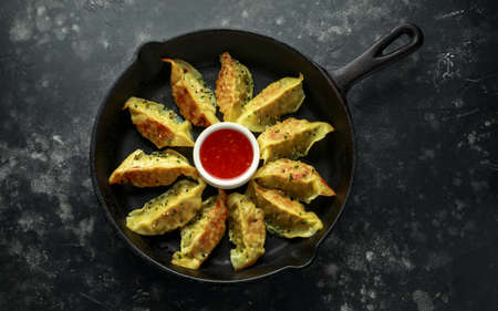 Fried yaki Gyoza served on cast iron skillet, pan with sweet chilli sauce and sesame seeds