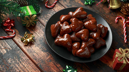 Christmas Gingerbread, lebkuchen heart with decoration, gifts, green tree branch on wooden rustic table Stockfoto