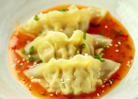 Steamed yaki Gyoza served on white plate with sweet chilli sauce and sesame seeds