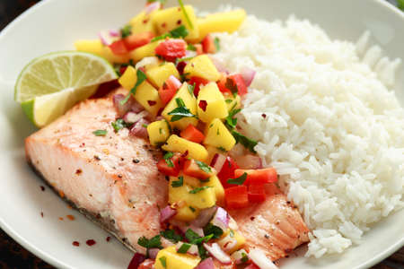 Salmon with mango salsa and white rice on plate Stock Photo