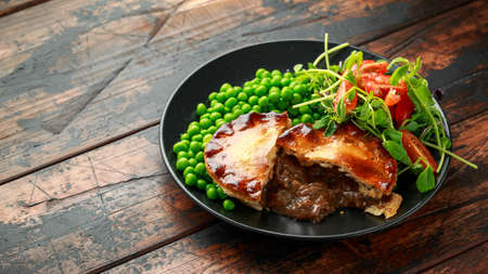 Beef steak pies with rich onion gravy served with sweet peas and salad