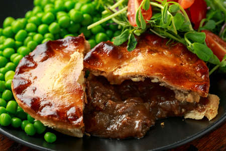 Beef steak pies with rich onion gravy served with sweet peas and salad 写真素材 - 134405810