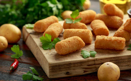 Homemade Potato Croquettes with dipping sauce on wooden board