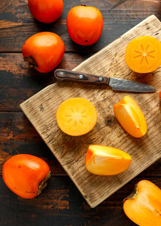 Raw ripe persimmons fruits slices on wooden board