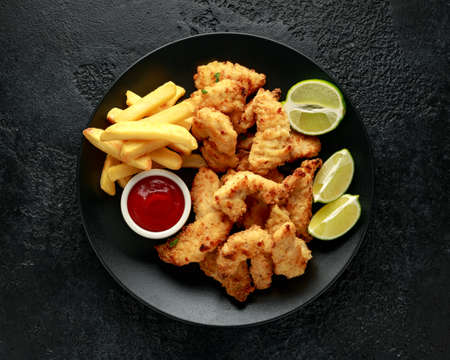 Buttermilk chicken nuggets served on black plate with lime wedges Standard-Bild