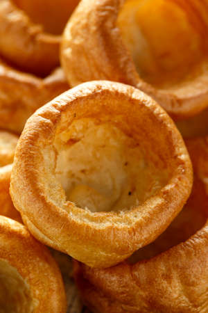 Traditional English Yorkshire pudding side dish on black plate and background.