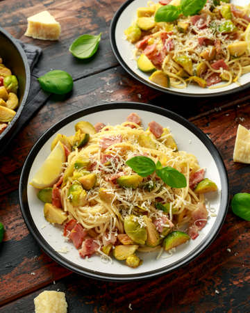 Homemade Brussels sprouts, bacon, pancetta pasta with parmesan cheese. On wooden table Banco de Imagens