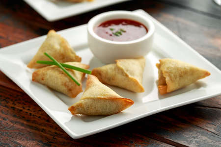 Fresh Indian Samosa with dipping sweet chili sauce Stock Photo