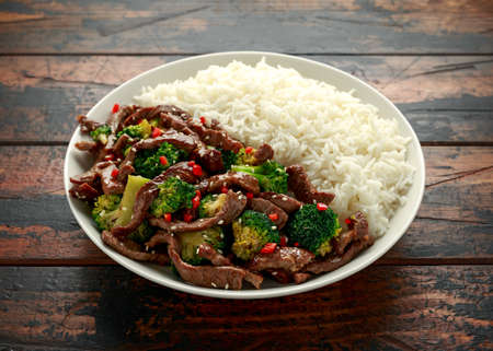 Homemade Beef and Broccoli with Rice on wooden table.