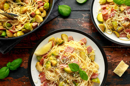 Homemade Brussels sprouts, bacon, pancetta pasta with parmesan cheese. On wooden table.