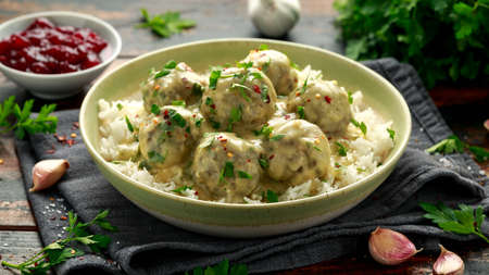 Hot Swedish meatballs with white rice and cranberry sauce on wooden table.