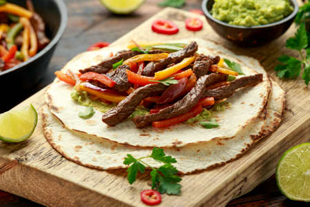 Beef Steak Fajitas with tortilla mix pepper, onion and avocado on wooden board. 版權商用圖片