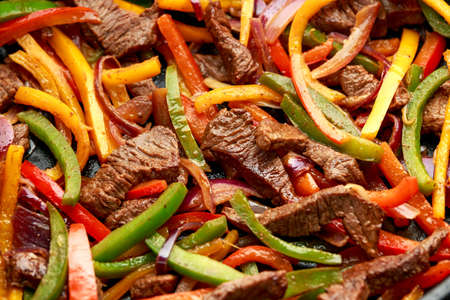 Beef Steak Fajitas with mix pepper, onion and avocado on wooden board.