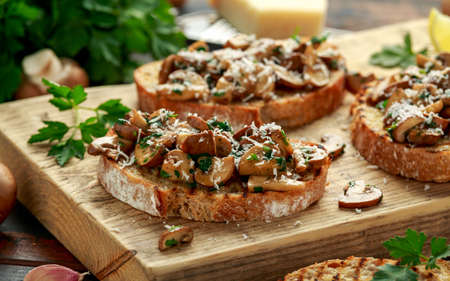 Grilled mushroom toast with parsley, lemon and parmesan cheese on wooden board. healthy vegan food.