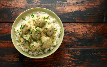 Hot Swedish meatballs with white rice on wooden table Stock Photo