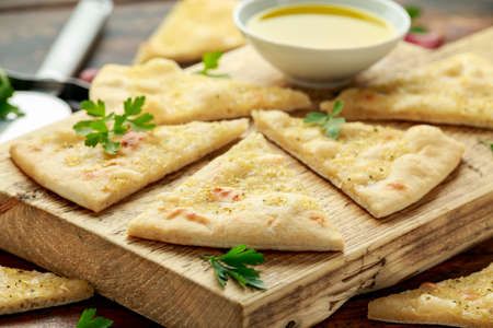 Fresh slices of Garlic pizza on wooden board with herbs