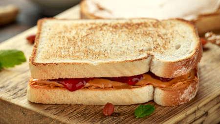 Sándwich de mantequilla de maní y mermelada de fresa sobre tabla de madera. desayuno de la mañana.