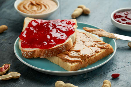 Peanut Butter and strawberry Jelly Sandwich in a blue plate. morning breakfast.