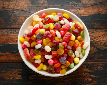 A mix of colorful candy in white bowl on wooden table