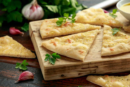 Fresh slices of Garlic pizza on wooden board with herbs. Imagens