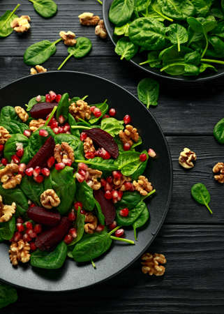 Healthy Beet Salad with fresh sweet baby spinach, pomegranate seeds and candy walnut. healthy Vegan vegetarian, plant based food