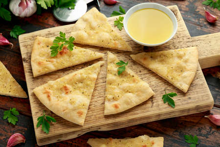 Fresh slices of Garlic pizza on wooden board with herbs.