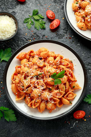 Conchiglie rigate pasta with chickpeas in tomato sauce with parmesan cheese. Healthy vegan food. Banco de Imagens