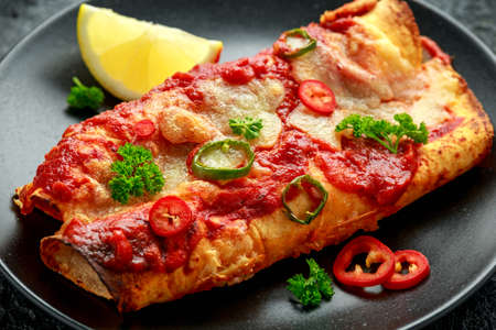 Baked Chicken fillets enchiladas with courgette, salsa sauce and cheese served with lemon wedges and chilies 스톡 콘텐츠
