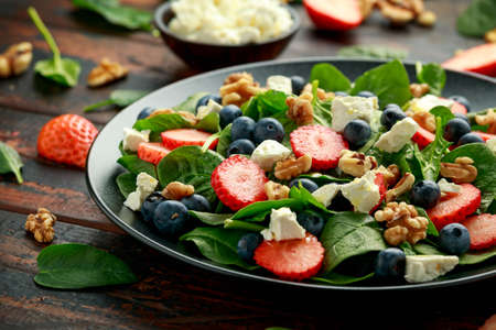Spinach, Strawberry, blueberry salad with walnut and feta cheese. Summer healthy food Banco de Imagens