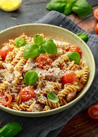Healthy Chicken, fusilli pasta with tomatoes, basil and parmesan cheese. on wooden table. 스톡 콘텐츠