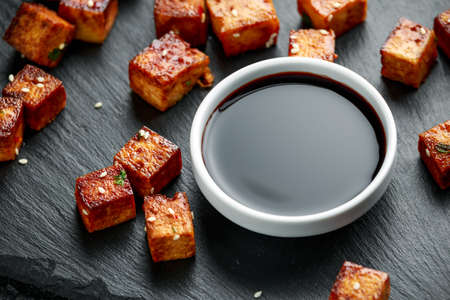 Fried Tofu with chopstick and sesame seeds on rustic stone board