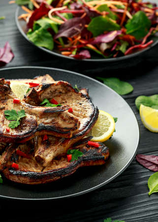 Homemade Grilled Pork loin chops in lemon sauce with herbs on rustic wooden table 스톡 콘텐츠