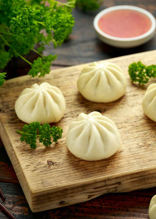 Steamed Buns with duck stuffing, chili sauce on wooden board. Asian food 스톡 콘텐츠