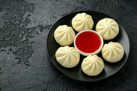 Steamed Buns with duck stuffing, chili sauce on black plate.