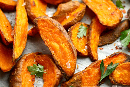 Healthy Baked Orange Sweet Potato wedges with dip sauce, herbs, salt and pepper Stock Photo