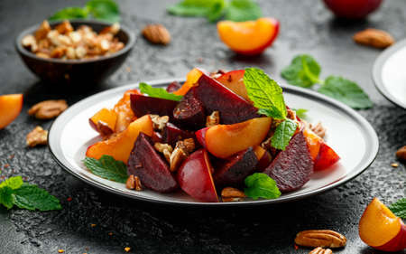 Vegan Plum, beet salad with pecan nuts, mint and herbs on rustic black table.