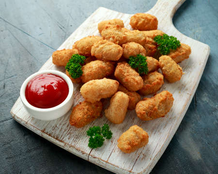 Crispy Battered scampi nuggets with ketchup on white wooden board Фото со стока