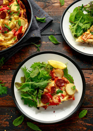Chorizo Frittata with salad on black and white plate. healthy morning breakfast food Imagens
