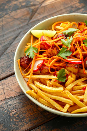Loaded French Vegan Fries with tofu, pickled vegetables radish, carrot and spicy hot sauce.