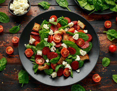 Chorizo Tomato salad with spinach, feta cheese and croutons. healthy summer food.